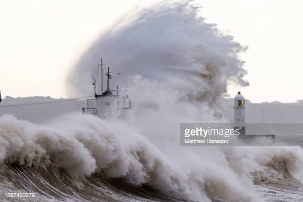 Waves crash agains the harbour wall on August 21, 2020 in Porthcawl, Wales. The Met Office have issued a yellow weather warning for wind with gusts...