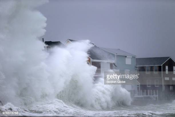 Waves crash against homes in Scituate MA during a nor'easter storm on March 2 2018