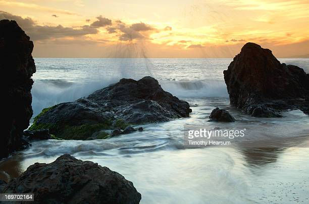 waves crash against lava rocks at sunset - timothy hearsum stock photos and pictures
