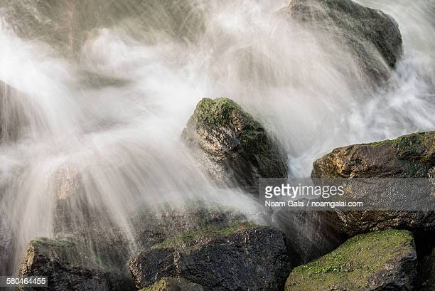 waves crash against rocks - noam galai stock pictures, royalty-free photos & images
