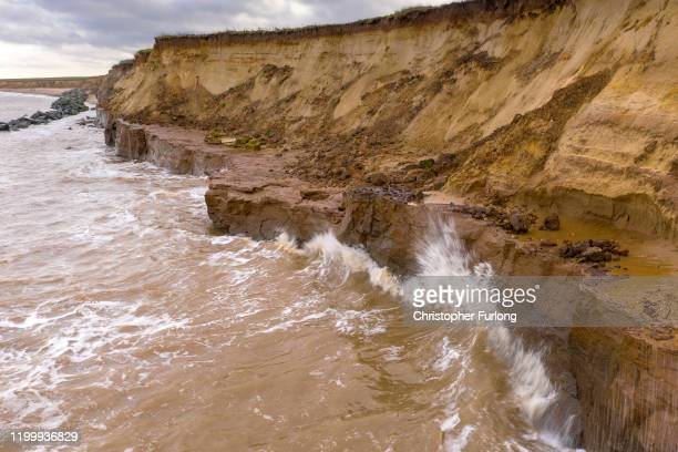 Waves crash against the eroding sandy cliffs in the coastal village of Happisburgh on January 16 2020 in Great Yarmouth United Kingdom The sea...