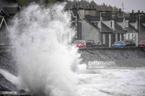 Waves crash against the harbour wall on February 15 2020 in Port William United Kingdom The Met Office has issued an amber alert for rain in parts of...