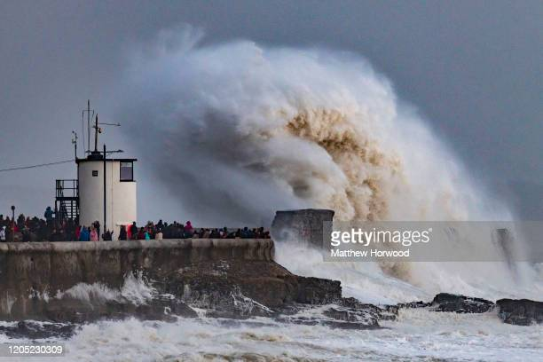 Waves crash against the harbour wall on February 9, 2020 in Porthcawl, United Kingdom. The Met Office have issued an amber weather warning for wind...