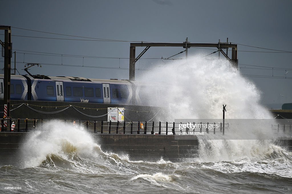 Waves crash against the sea wall as a train passes through on November 13, 2015 in Saltcoats, Scotland. Storm Abigail has closed schools on the Western Isles and ferries have been cancelled as gale force winds overnight left 12,000 properties without power.