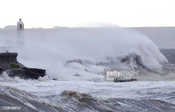 Waves crash against the sea wall at Porthcawl, south Wales, on August 21, 2020 as Storm Ellen brings high winds across the country. - Weather...