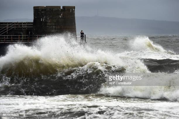 TOPSHOT Waves crash as the remnants of Storm Ophelia hit Saltcoats on the west coast of Scotland on October 17 2017 Train services between Glasgow...