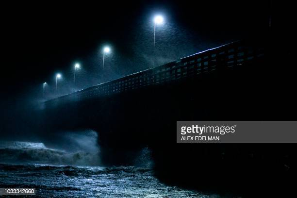TOPSHOT Waves crash into the Second Avenue Pier as Hurricane Florence makes landfall late on September 14 2018 in Myrtle Beach South Carolina A woman...