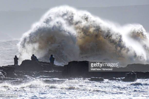 Waves crash near the harbour wall as people look on during Storm Gareth on March 13 at Porthcawl Wales The Met Office have issued a yellow weather...