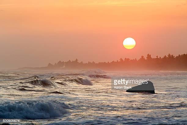 Waves crash on lone boulder at sunset