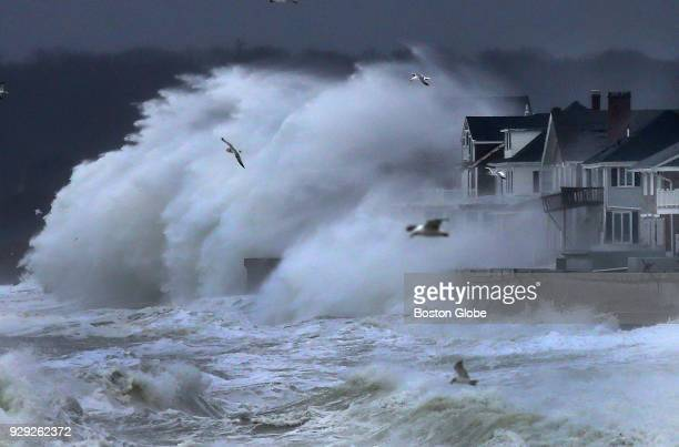Waves crash onto oceanfront homes along Surfside Road in Scituate MA as high tide and a nor'easter storm approach on March 7 2018