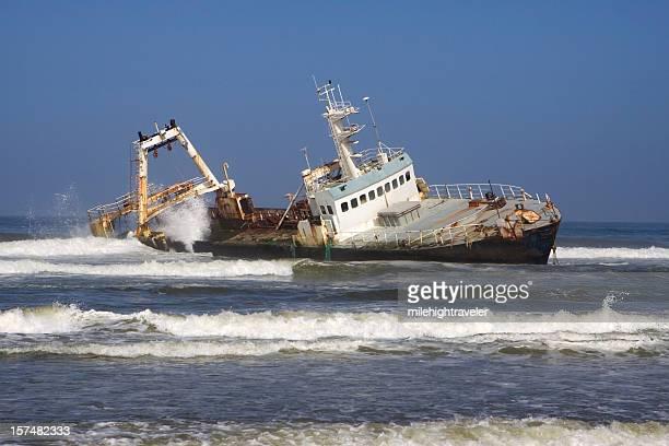 Waves crash over fishing trawler shipwreck Skeleton Coast Namibia