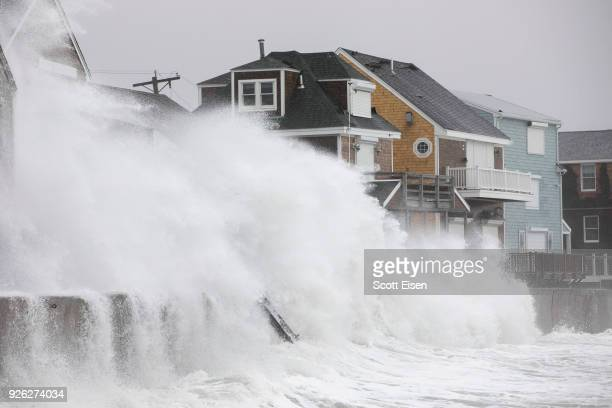 Waves crash over houses on Turner Rd as a large coastal storm affects the area on March 2 2018 in Scituate Massachusetts A powerful nor'easter is...