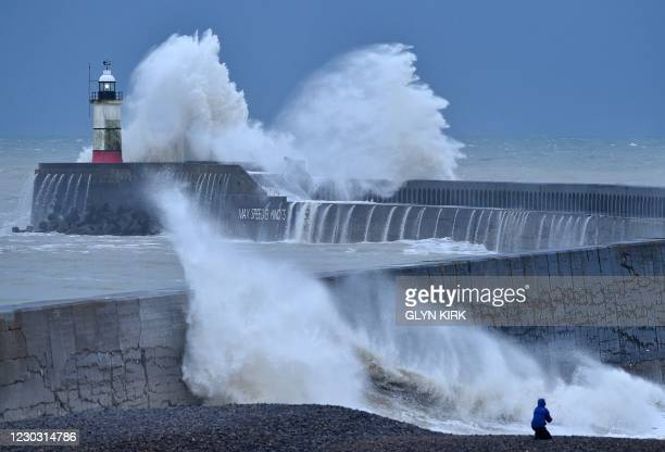 Waves crash over Newhaven Lighthouse and the harbour wall on the south coast of England on December 27 as Storm Bella brings rain and high winds to...
