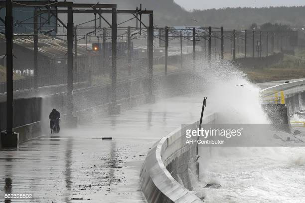 TOPSHOT Waves crash over the breakwater as the remnants of Hurricane Ophelia hit Saltcoats on the west coast of Scotland on the morning of 17th...
