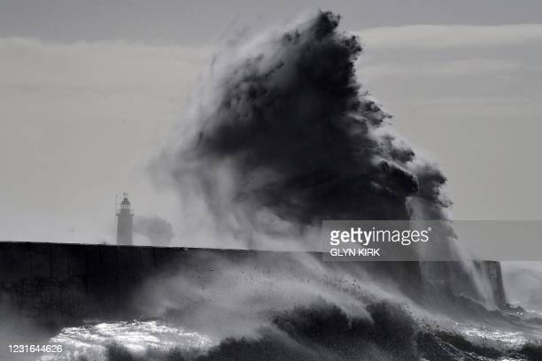 Waves crash over the harbour wall in Newhaven, south coast of England on March 11, 2021 as heavy gusts hit the south coast.