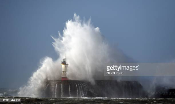 Waves crash over the harbour wall in Newhaven, southern England on March 11, 2021 as heavy gusts hit the south coast.