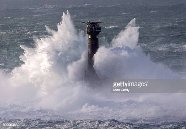 Waves crash over the Longships Lighthouse just off Land's End on February 8 2016 in Cornwall England Parts of the UK are currently being battered by...