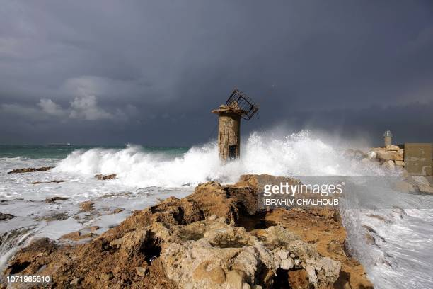 Waves crash over the old lighthouse and spill to the other side at the port of the Lebanese city of Batroun north of Beirut on December 12 2018