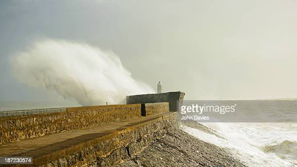 Waves crash over the Porthcawl sea wall during. A very stormy Autumn Sunday in October.