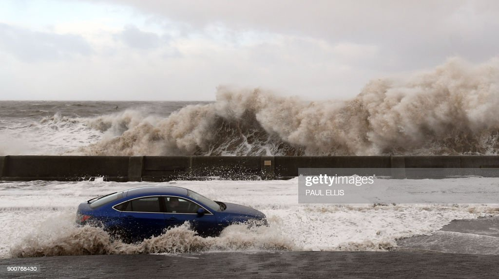 Waves crash over the tidal wall as a motorist travels along the coastal road in New Brighton, north west England, on January 3, 2018, as Storm Eleanor swept over the country. Storm Eleanor swept across the country overnight, bringing winds of up to 100 mph in places and carrying rain, hail and thunder and lightning. / AFP PHOTO / Paul ELLIS