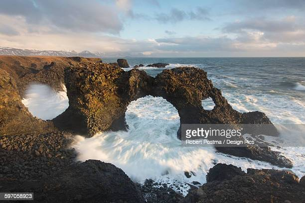 Waves Crash Through A Natural Archway Near Arnarstapi On The Snaefellsnes Peninsula