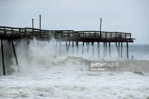 Waves crash under the Avalon Pier that was damaged by Hurricane Dorian on September 6, 2019 in Kill Devil Hills, North Carolina. Dorian passed...