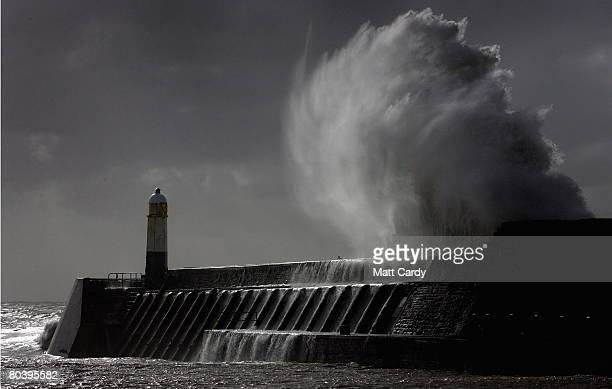 A waves crashes over the harbour wall on the seafront at Porthcawl on March 12 2008 in Wales United Kingdom The British Isles is being battered for...