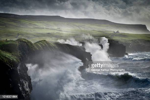 waves crashing against the cliffs of moher, doolin, clare, ireland - irlanda fotografías e imágenes de stock