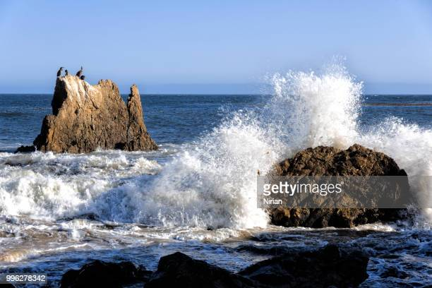 waves crashing against the rocks - malibu beach stock pictures, royalty-free photos & images