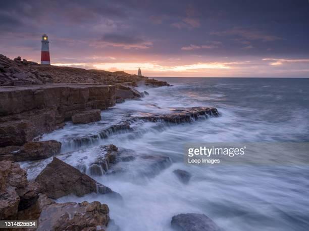 Waves crashing below a lighthouse at sunrise.
