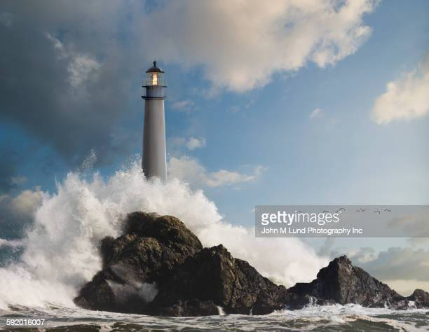 Waves crashing on lighthouse and rock formations