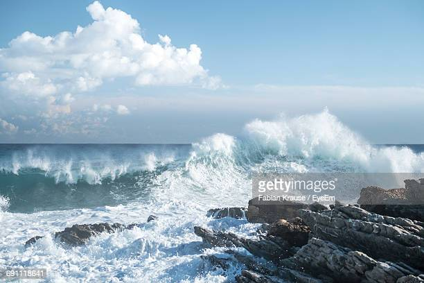 waves crashing on rock against cloudy sky - seascape stock pictures, royalty-free photos & images