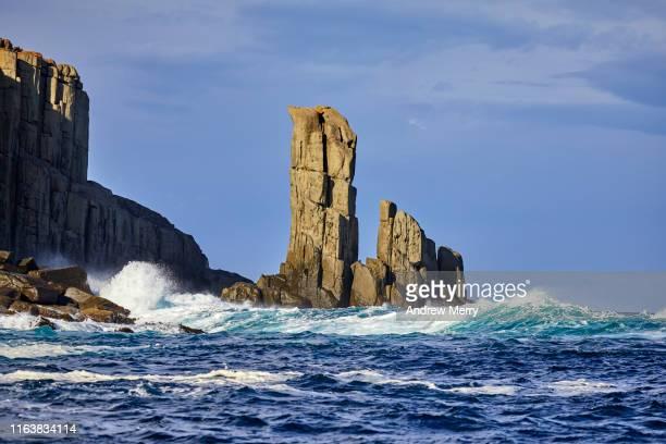 waves crashing on rock formations at sea coastline with blue sky, australia - 南極海 ストックフォトと画像
