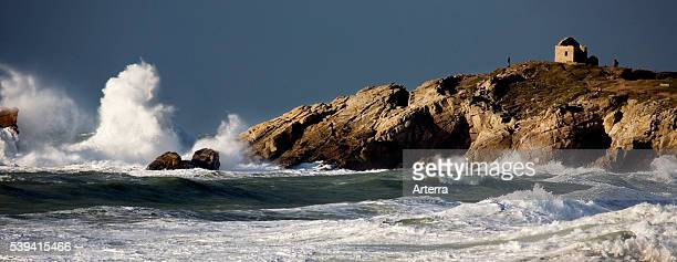 Waves crashing on rocky shore during storm at sea in winter Cote Sauvage Quiberon Brittany France