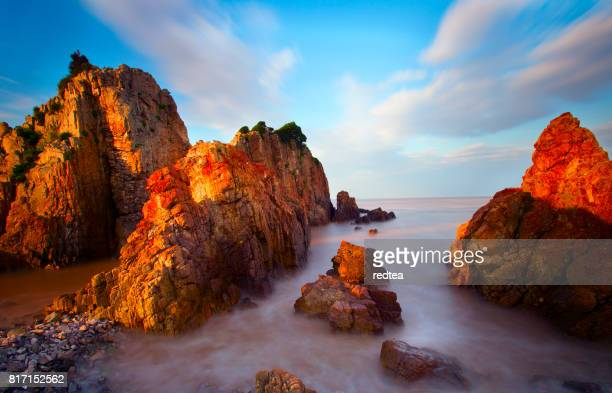 Waves crashing on rocky shore in the sunset