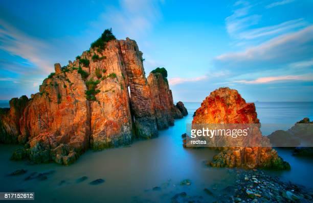 Vågorna kraschar på klippor i solnedgången