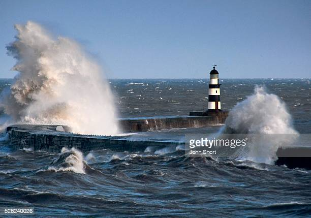 waves crashing on seawall - seawall stock pictures, royalty-free photos & images