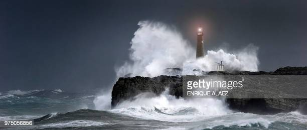 waves crashing over a lighthouse during a storm. - breaking wave stock pictures, royalty-free photos & images