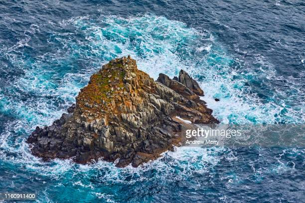 waves crashing over small rocky island, aerial view, closeup - resilience stock photos and pictures