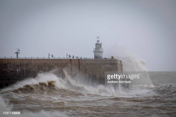 Waves cresting over Folkstone Harbour Arm on the south coast of England as a major storm swept over the country on 11th of March 2021, in Folkestone,...