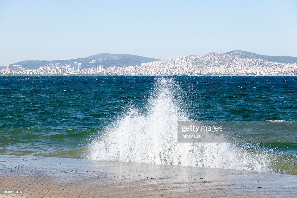 Waves Crushing to Pier with Urban Background Scene : Stock Photo
