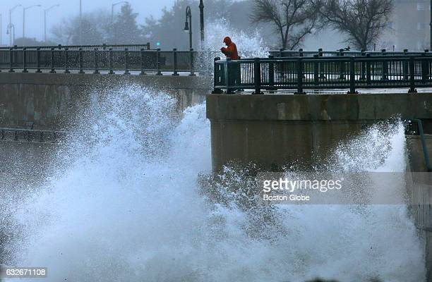 Waves from a nor'easter storm pound the seawall in the morning next to King's Beach along Lynn Shore Drive in Lynn MA as a brave soul takes photos on...