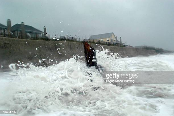Waves hammer a berm formed by erosion from the the heavy winds and rough waters brought on by Hurricane Ophelia tearing away a protective dune fence...