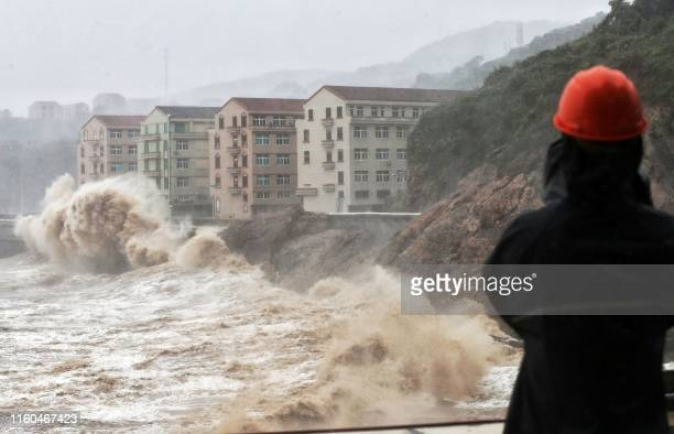 Waves hit a sea wall in front of buildings in Taizhou China's eastern Zhejiang province on August 9 2019 China issued a red alert for incoming Super...