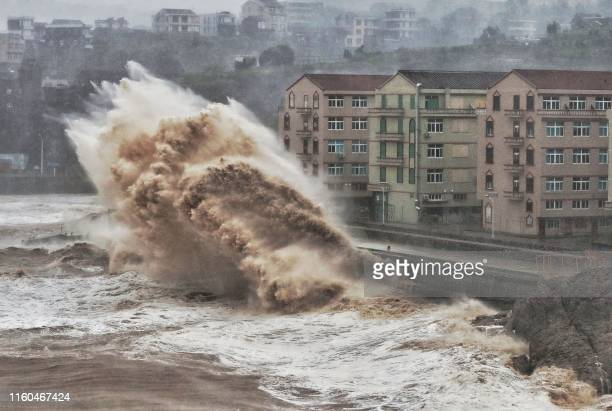 TOPSHOT Waves hit a sea wall in front of buildings in Taizhou China's eastern Zhejiang province on August 9 2019 China issued a red alert for...