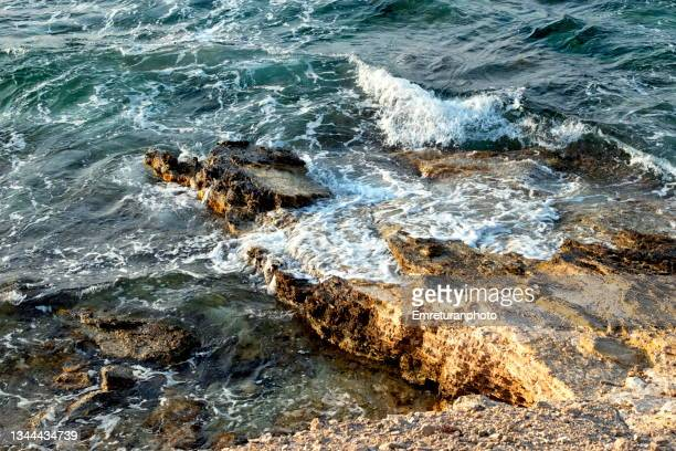waves hitting rock formations along the coast in çeşme. - emreturanphoto stock pictures, royalty-free photos & images