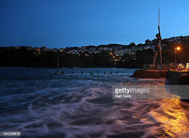 Waves lap beneath the harbour wall beside Damien Hirst's bronze sculpture of a pregnant woman on October 16 2012 in Ilfracombe England The bronzeclad...
