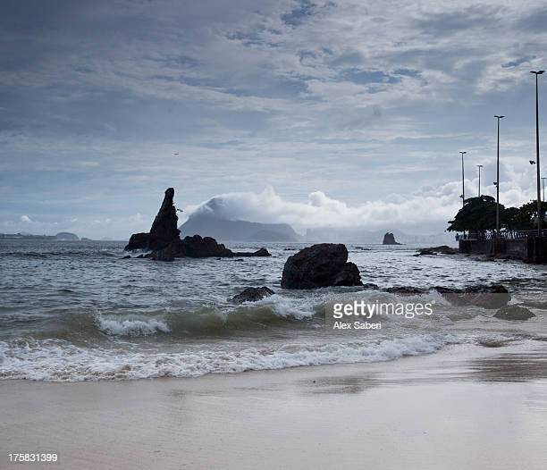 waves lap onto the sandy beach in niteroi. - alex saberi stock pictures, royalty-free photos & images