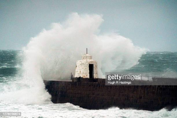 Waves lash into the iconic Monkey Hut building at Portreath Harbour as winds from Storm Alex cause severe weather on October 3, 2020 in Portreath,...