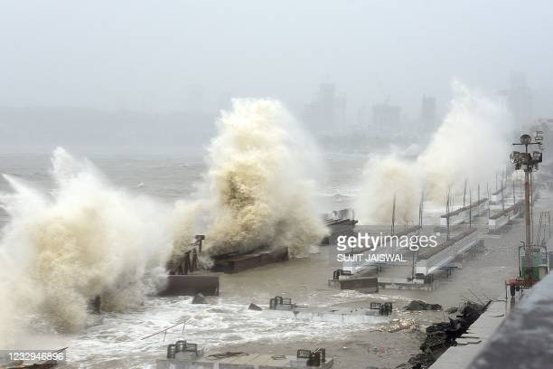 Waves lash over onto a shoreline in Mumbai on May 17 as Cyclone Tauktae, packing ferocious winds and threatening a destructive storm, surge bore down...